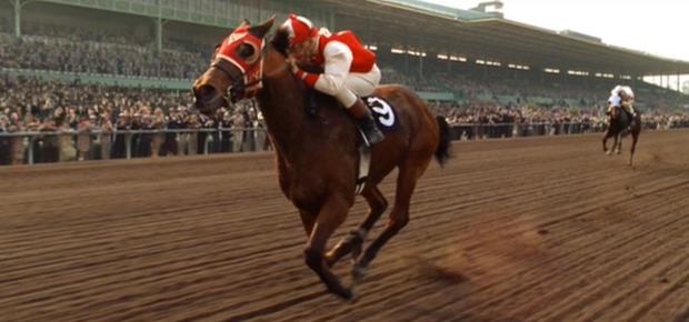Seabiscuit met jockey 'Red' Pollard in winnende positie op weg naar de finish.
